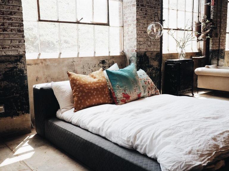 кровать на фоне кирпичной кладки
